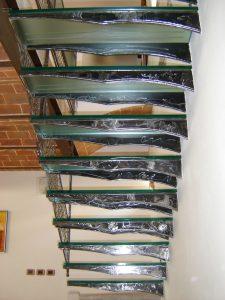 Scala da interno con gradini in vetro e struttura in ferro molato